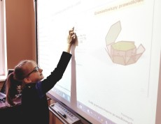 Uczennica wykorzystuje tablicę interaktywną do obliczania objętości