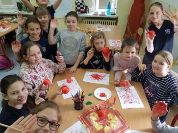 Uczennice przygotowują czerwone jabłuszka do scenografii teledysku
